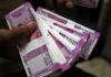 FILE PHOTO: A cashier displays the new 2000 Indian rupee banknotes inside a bank in Jammu